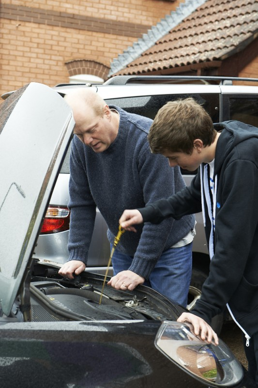 Foster carer and teenager checking the oil in a car engine