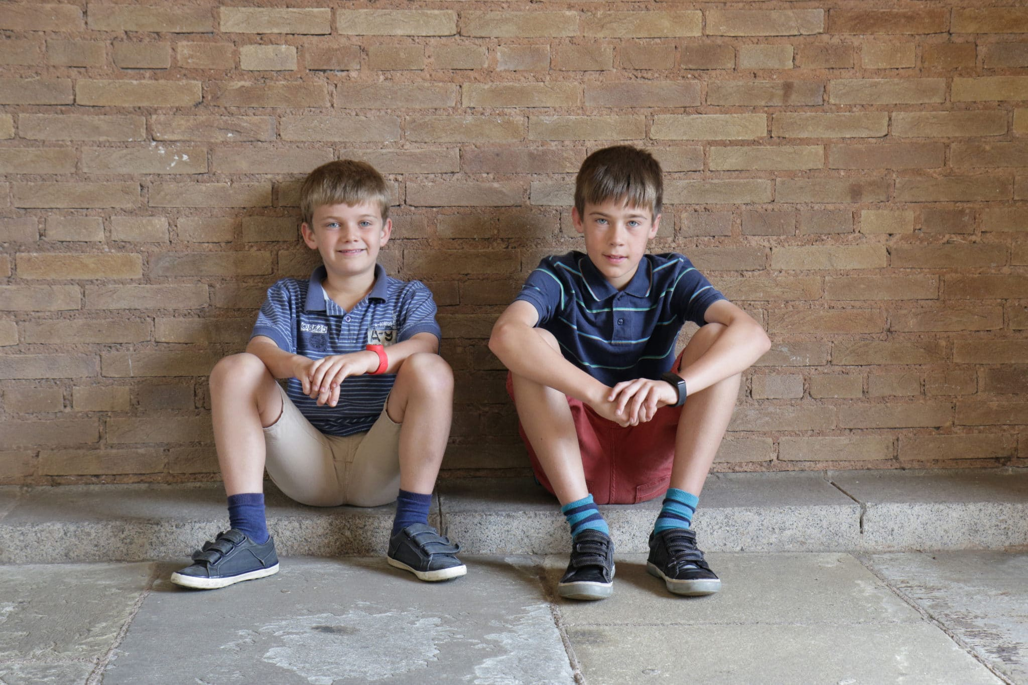 Two boys sitting on the floor leaning against a wall